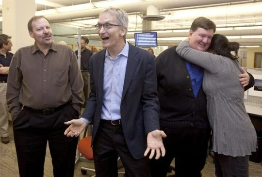 Seattle Times investigations editor James Neff (second from left) celebrates the Pulitzer announcement, along with investigative reporters Ken Armstrong, left, and Michael J. Berens. Reporter Christine Clarridge gives Berens a hug.